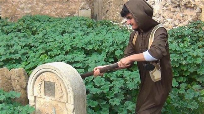 A Takfiri destroying ancient Christian graves in the northern Mosul,Iraq